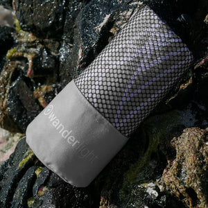 grey towel in pouch nestled among rocks on the shore