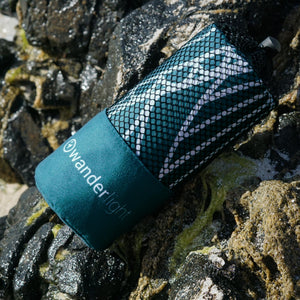 teal towel in pouch nestled among rocks on the shore