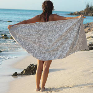 woman standing on shore with arms outstretched holding grey towel with mandala print