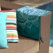 Load image into Gallery viewer, teal towel with mandala print folded and draped over the side of a couch arm with pool in background