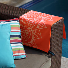 Load image into Gallery viewer, orange towel with mandala print folded and draped over the side of a couch arm with pool in background