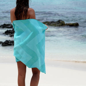 woman standing facing ocean with turquoise towel wrapped around body