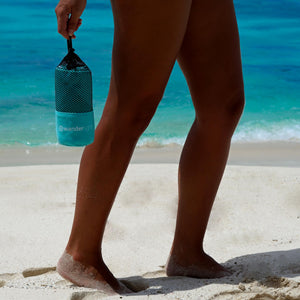 bottom half profile of woman walking along shore with turquoise towel pouch in hand