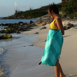 woman standing on rocky shoreline with turquoise towel draped over forearm