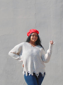 red beret hat, distressed cream sweater  and jeans.