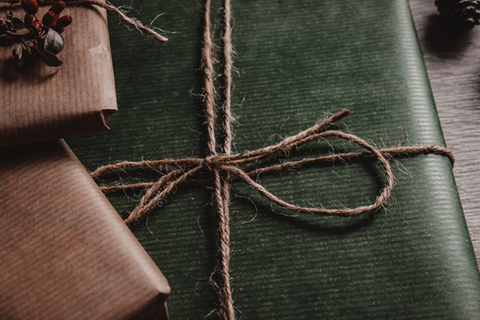 Gifts wrapped in green and brown paper with a twine bow