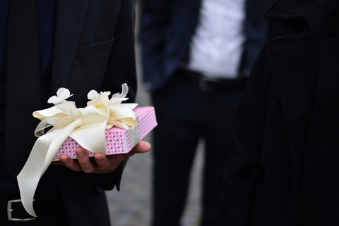 Man holding a gift box wrapped in pink paper and a white ribbon