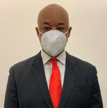 Load image into Gallery viewer, African American man in a suit wearing a KN95 face mask from C19PPE.org.  It has ear loops to hold the face-mask tight to your face, is made of a soft material & has a thin metal band to help seal around your nose.  The protective face mask helps protect you and your family from COVID-19 virus by filtering up to 95 percent of particles you breathe in. Cloth face masks do not filter the air that your breathe in and therefore do little to protect you and your family from COVID-19 virus.