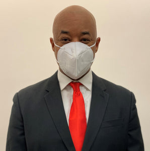 African American man in a suit wearing a KN95 face mask from C19PPE.org.  It has ear loops to hold the face-mask tight to your face, is made of a soft material & has a thin metal band to help seal around your nose.  The protective face mask helps protect you and your family from COVID-19 virus by filtering up to 95 percent of particles you breathe in. Cloth face masks do not filter the air that your breathe in and therefore do little to protect you and your family from COVID-19 virus.