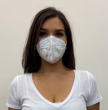 Cargar imagen en el visor de la galería, Woman, long dark hair in a white top, wearing a KN95 face mask from C19PPE.org. The face-mask has an exhaust vent valve & ear loops to hold the face mask tight to her face. It helps protect you from COVID-19 virus by filtering up to 95 percent of particles you breathe in. Exhaust valve vents the hot moist air you breathe out so your glasses don't fog up as much & minimizes the formation of pimples from the hot moist air. Made of a soft material & has a thin metal band to help seal around your nose.