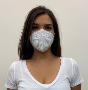 Woman, long dark hair in a white top, wearing a KN95 face mask from C19PPE.org. The face-mask has an exhaust vent valve & ear loops to hold the face mask tight to her face. It helps protect you from COVID-19 virus by filtering up to 95 percent of particles you breathe in. Exhaust valve vents the hot moist air you breathe out so your glasses don't fog up as much & minimizes the formation of pimples from the hot moist air. Made of a soft material & has a thin metal band to help seal around your nose.