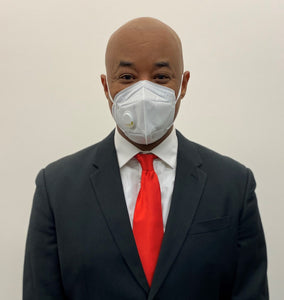 African American man in a suit wearing a KN95 face mask from C19PPE.org. The face-mask has an exhaust vent valve & ear loops to hold the face mask tight to his face. It helps protect you from COVID-19 virus by filtering up to 95 percent of particles you breathe in. Exhaust valve vents the hot moist air you breathe out so your glasses don't fog up as much & minimizes the formation of pimples from the hot moist air. Made of a soft material & has a thin metal band to help seal around your nose.