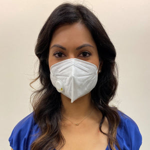 Woman, long dark hair in a blue top, wearing a KN95 face mask from C19PPE.org.  The face-mask has an exhaust vent valve & ear loops to hold the face mask tight to her face.  It helps protect you from COVID-19 virus by filtering up to 95 percent of particles you breathe in.  Exhaust valve vents the hot moist air you breathe out so your glasses don't fog up as much & minimizes the formation of pimples from the hot moist air.  Made of a soft material & has a thin metal band to help seal around your nose.