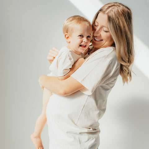 pregnant mother wearing organic everyday tee holding toddler son wearing organic everyday onesie
