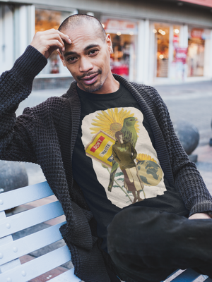 Black man wearing eco-friendly graphic tee sitting on city bench. Graphic tee depicts Black woman wearing a hoodie, a bird, a sign, a globe, and a sunflower.