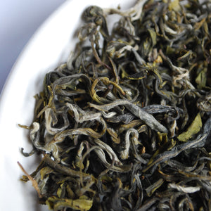 Closeup of loose dried tea leaves in a white bowl