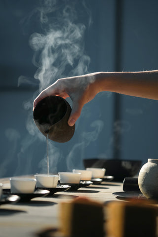 Outstretched hand holding a black tea pot pouring steaming hot tea into teacups against a dark blue background