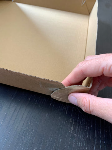 Attach cardboard box corners with tape for DIY shadow puppet theatre