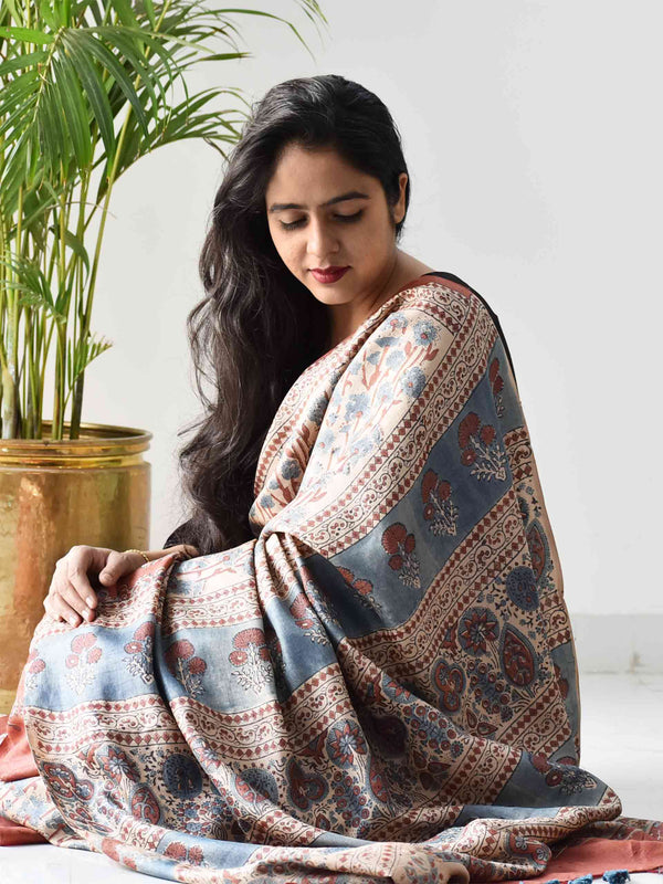 Cream Ajrakh handwoven tussar silk saree sitting pose at home