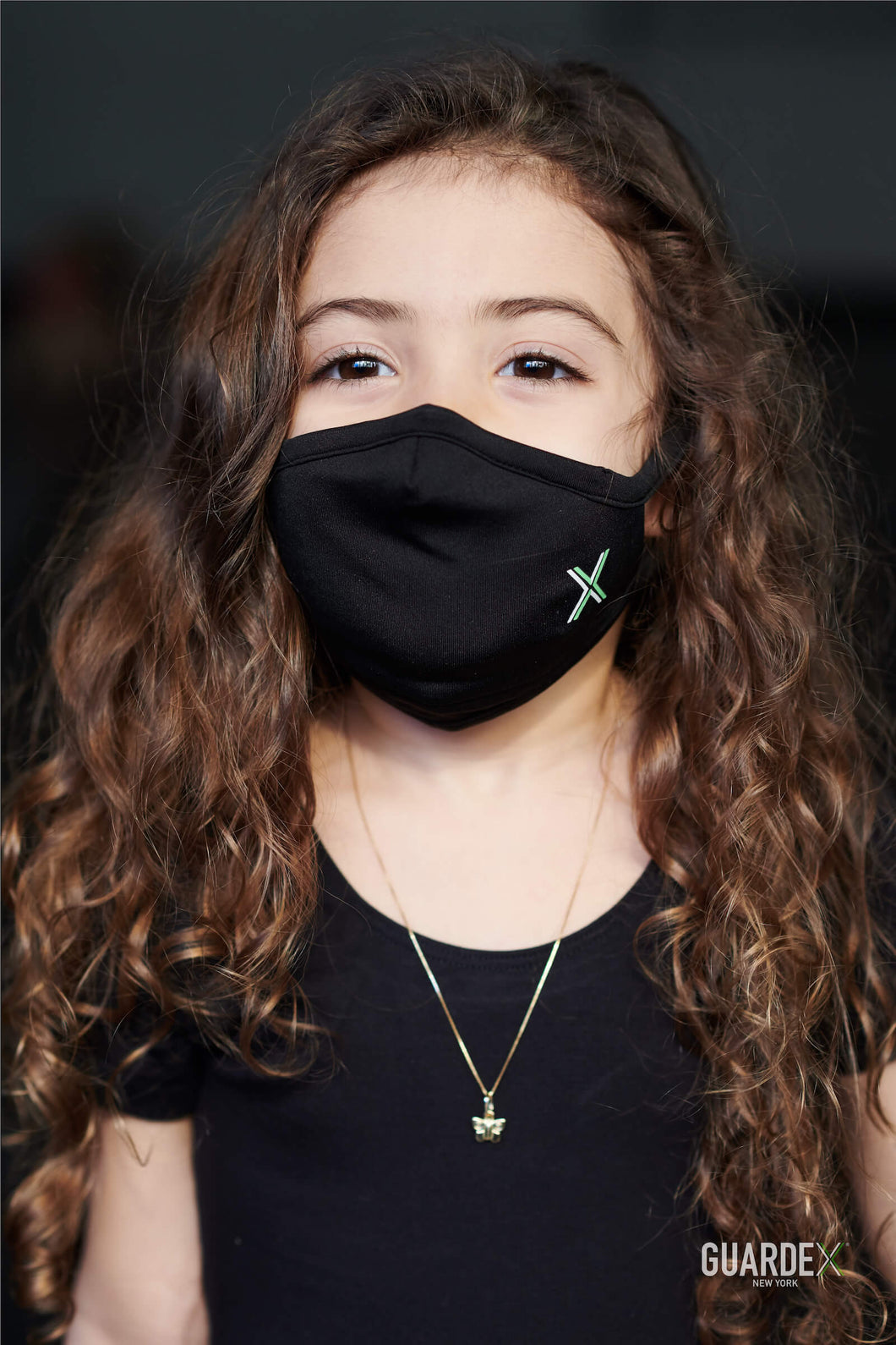 Little girl wearing Guardex Petite Face Mask plus 5 Protex Filters in black - adjustable, comfortable, for children ages 4 and up, teens, and adults who prefer a petite fit