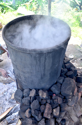salty black tea being preapred in a barrell for the tea workers on the estate in Assam, India