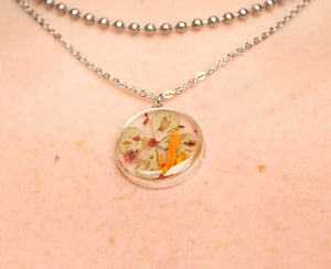 Real Four Leaf Clover, Sorrel Flower Buds and Biden Flower Petals set in crystal clear resin in a .925 sterling silver bezel.   The resin work is done completely by hand.