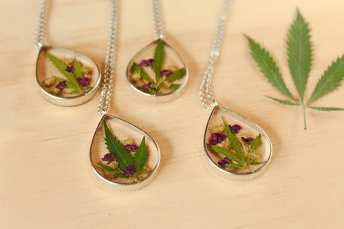 Real preserved leaf, Alyssum flowers and Goldenrod Flowers set in between layers of crystal clear resin in a silver teardrop pendant.