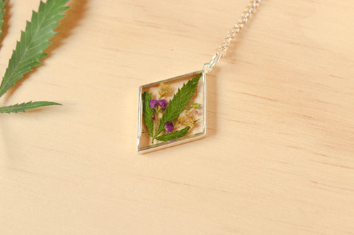 Real Cannabis Leaves, Alyssum flowers and Goldenrod Flowers set in crystal clear resin in a .925 sterling silver bezel.