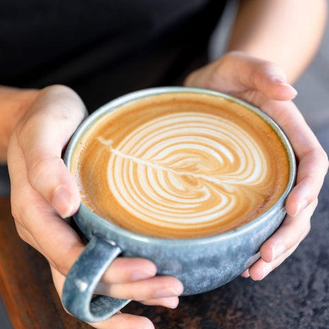 Person holding coffee with latte art