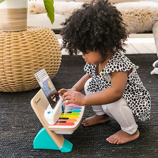 baby einstein young girl playing a toy piano