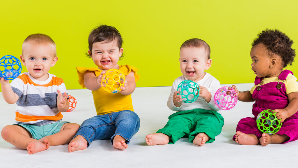 babies with toy balls laughing