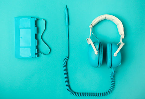 teal headphones and cassette podcast