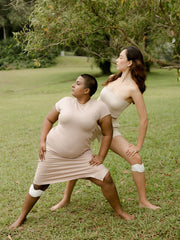 two women using kneeheat while stretching on an empty field