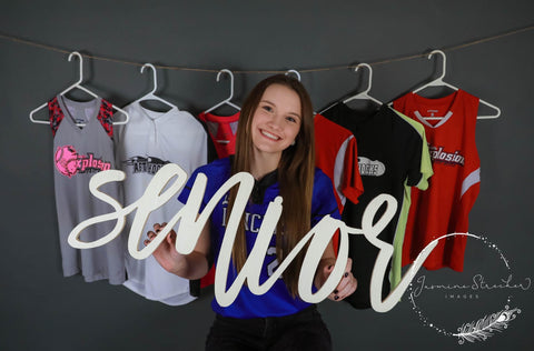 Senior wood prop with senior athlete in front of jerseys