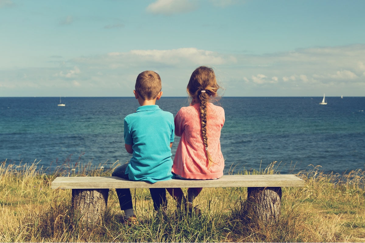 boy and girl sitting on a bench looking at the sea