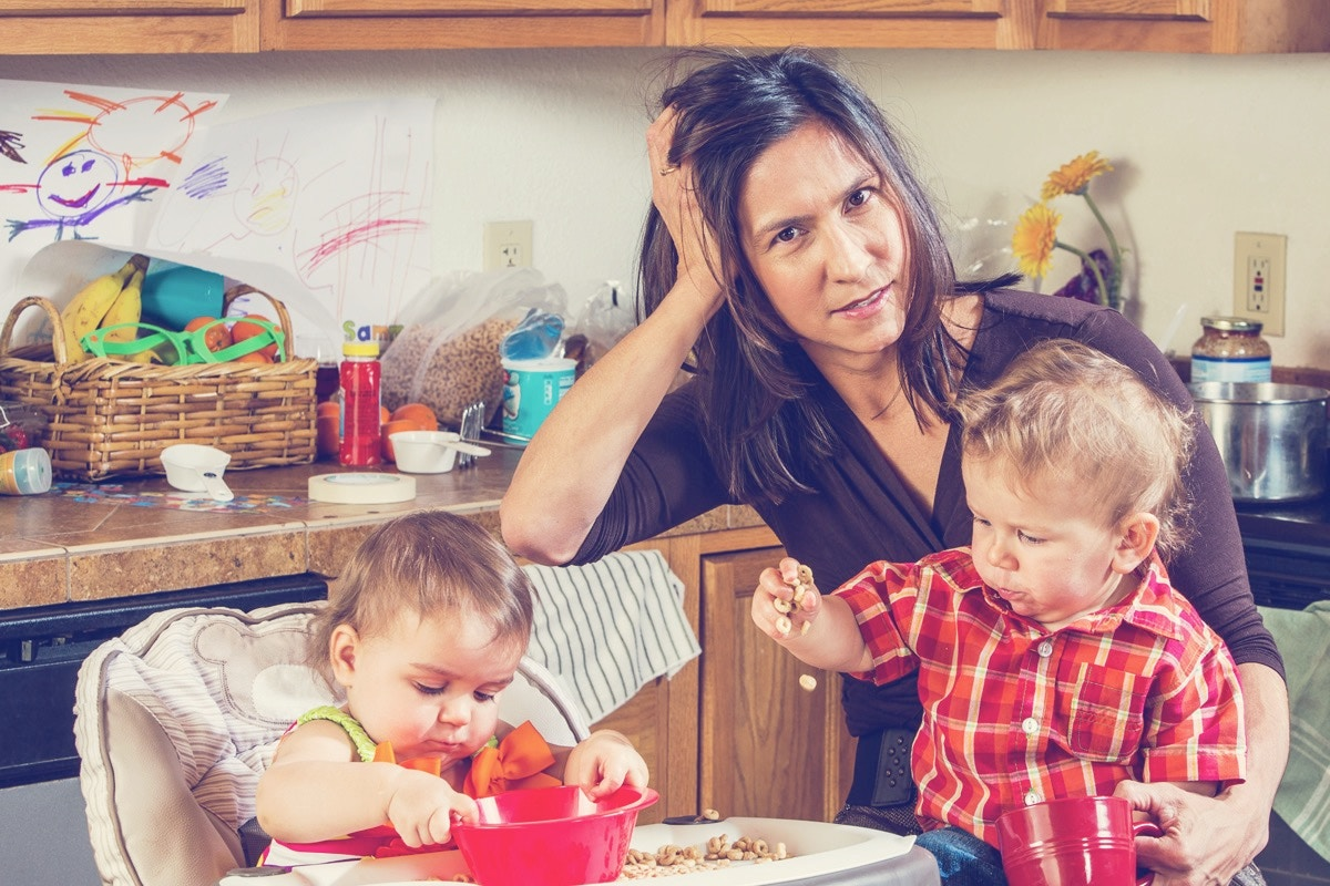 mom with two toddlers in a kitchen looking frustrated