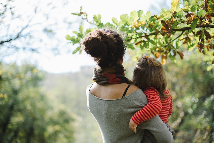 woman holding a baby girl looking at the leaves on trees