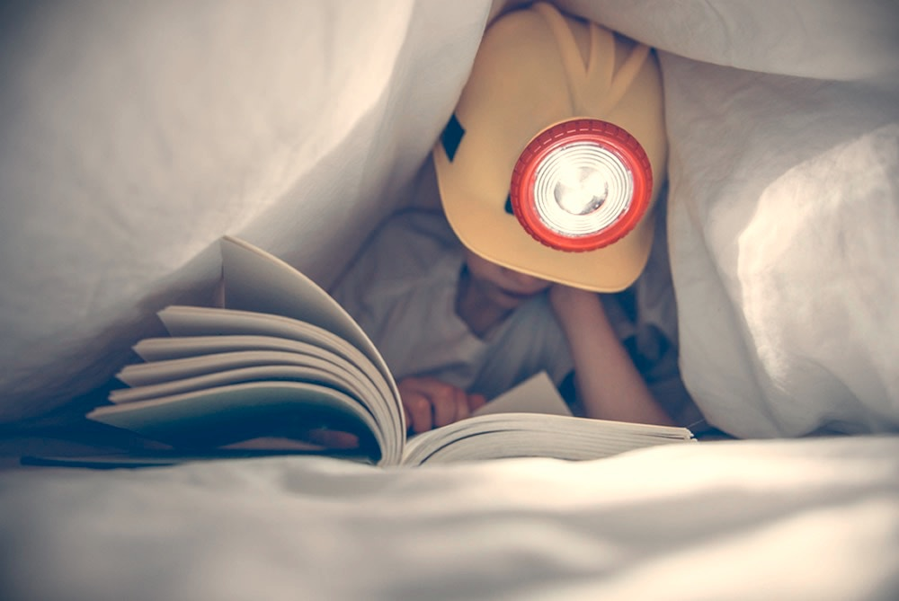 young boy with construction hat under his bed sheets reading a book with a flash light
