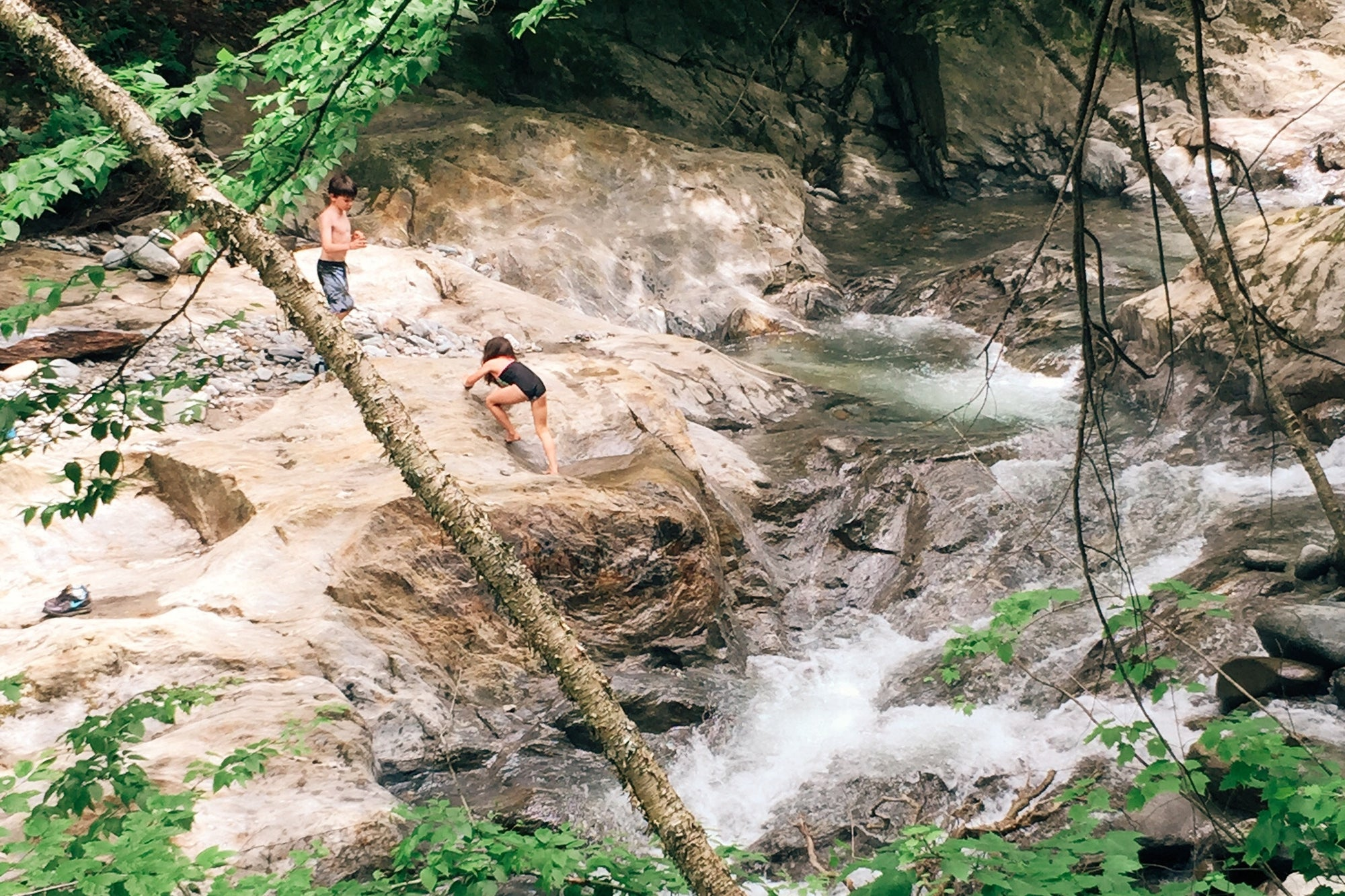young boy and girl climbing a rock with a stream near by