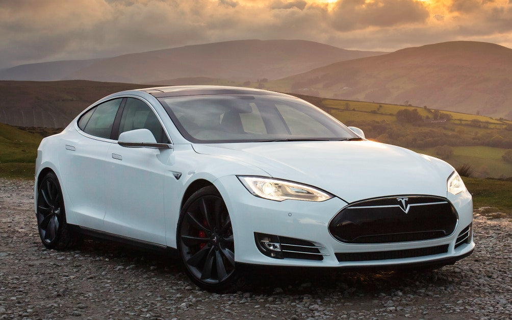 white tesla with mountains in the background