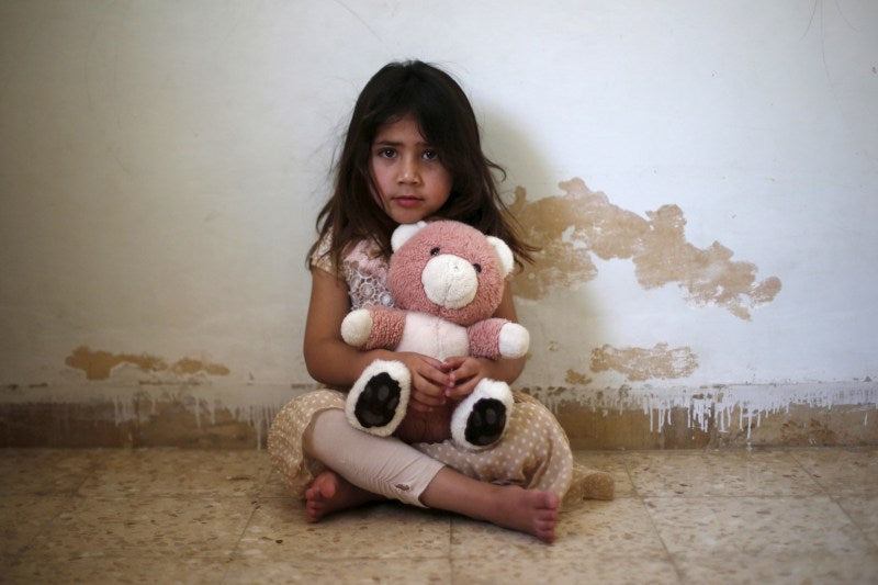 young girl holding a pink teddy bear