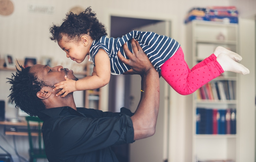 father holding baby daughter in the air