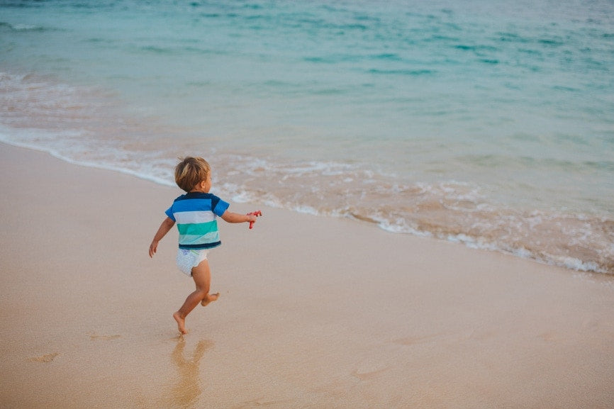 Little boy running and jumping at sea shore.