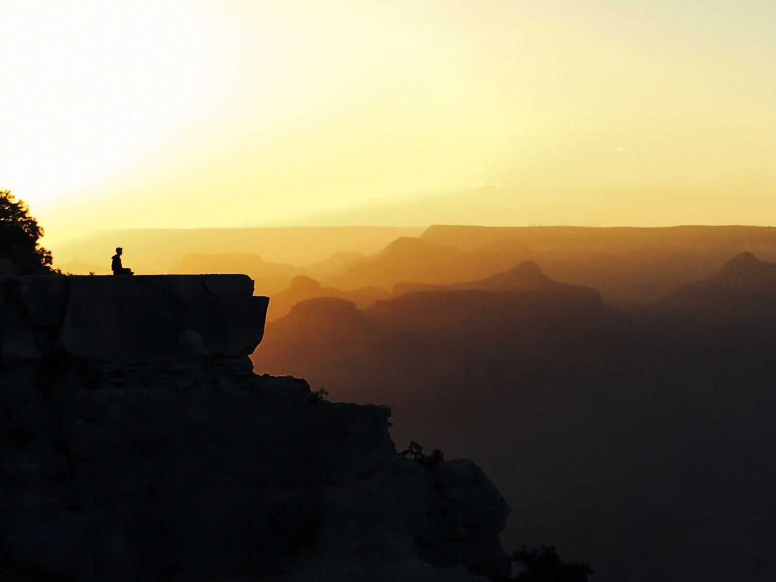 man sitting alone on mountain background is sunset