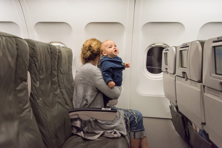 mother holding her baby in airplane