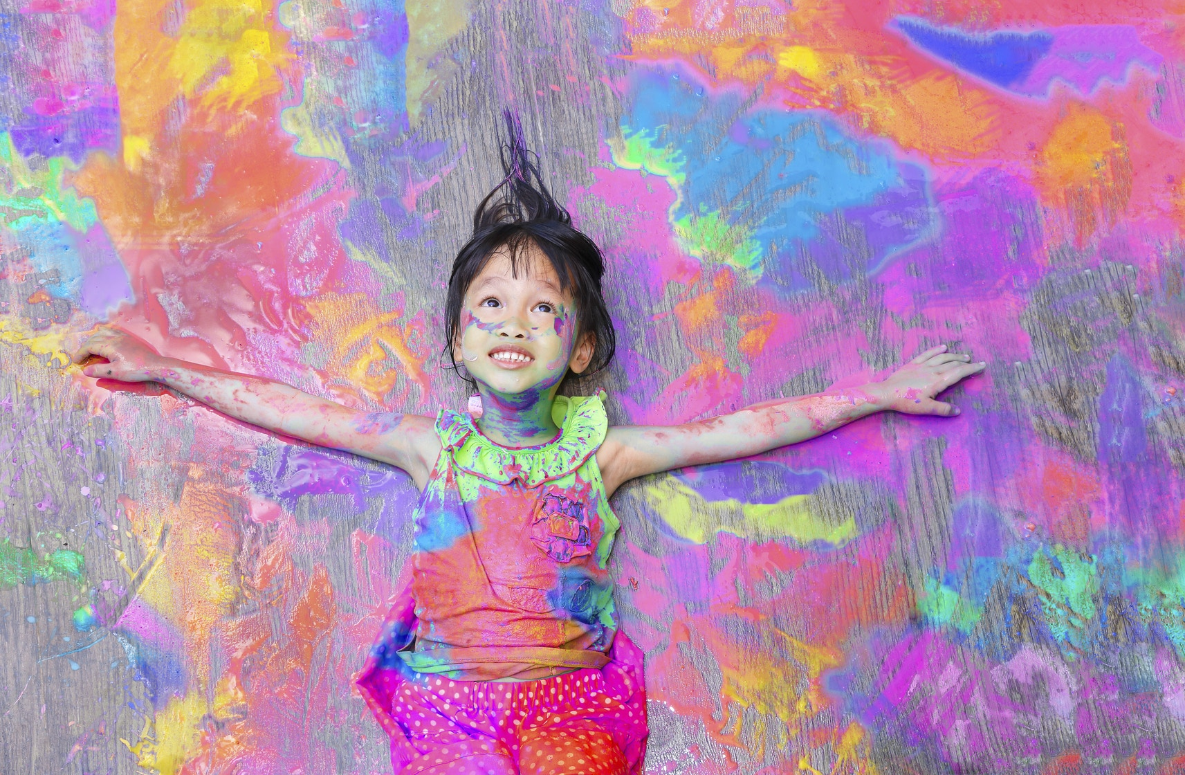 girl covered in paint lying on splattered paint background