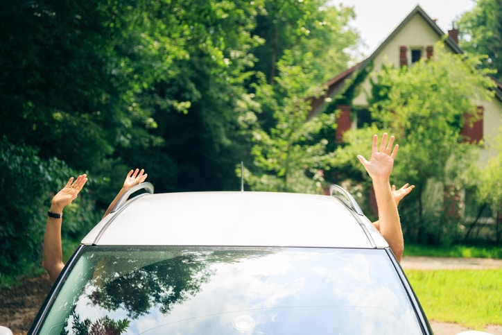 People waiving hand from a car