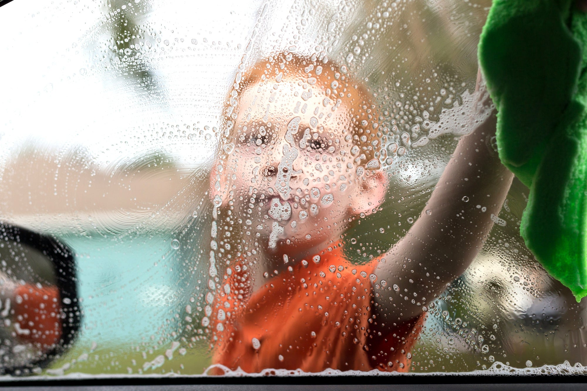 A child washing a car's window