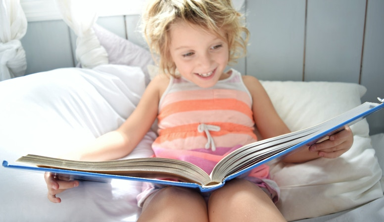 little girl reading book in bed