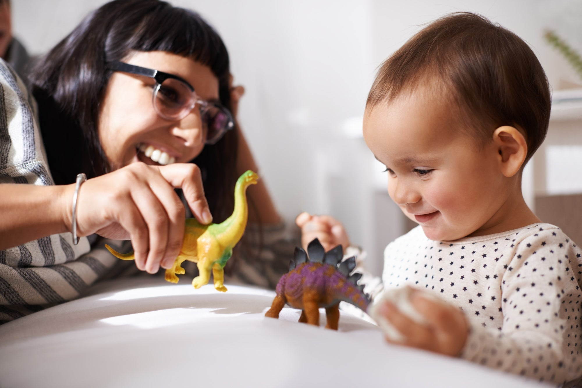 mom and child playing with colorful toy dinosaurs